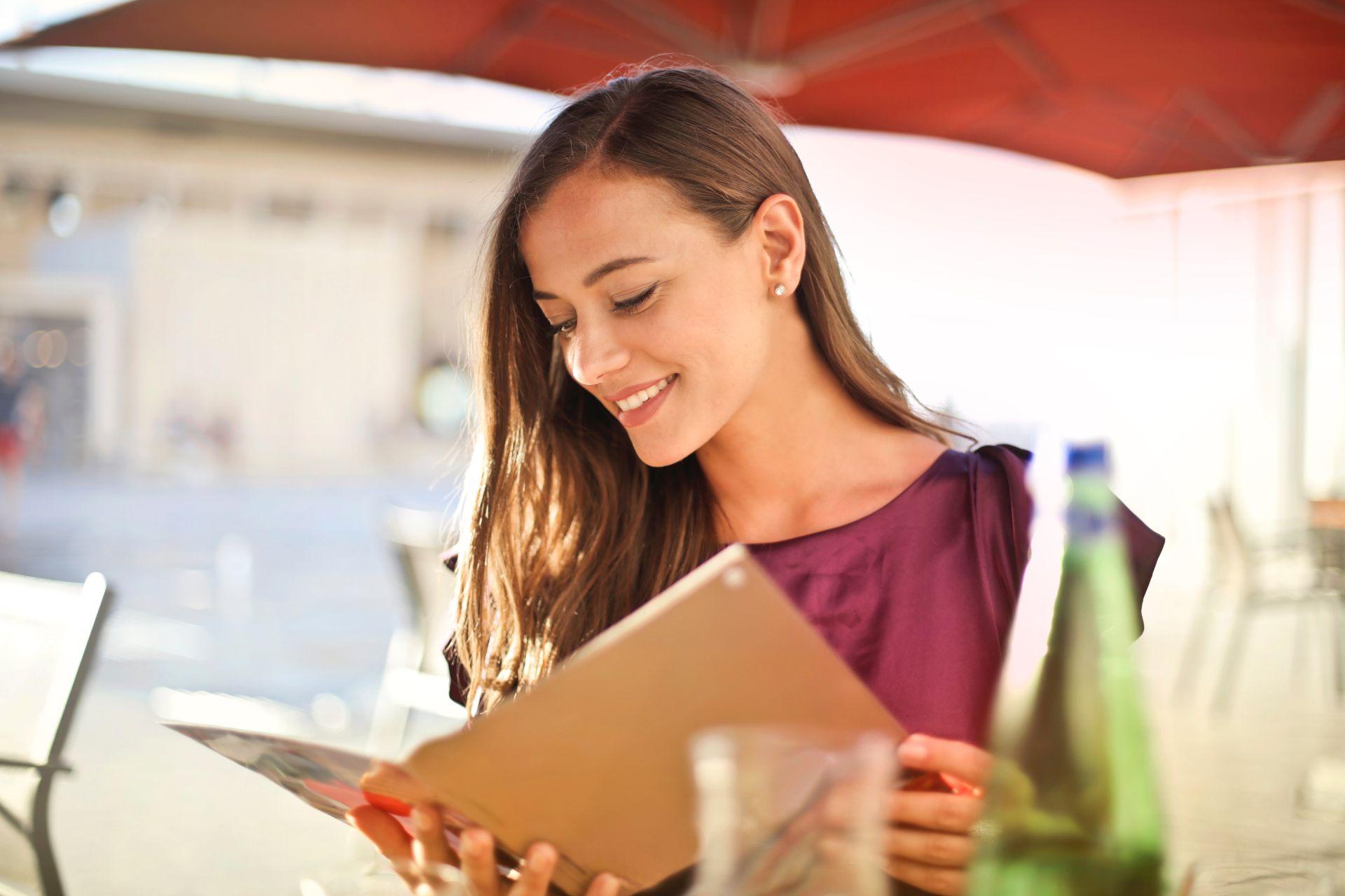 uśmiechnięta dziewczyna czytająca książkę - zdjęcie wprowadzające