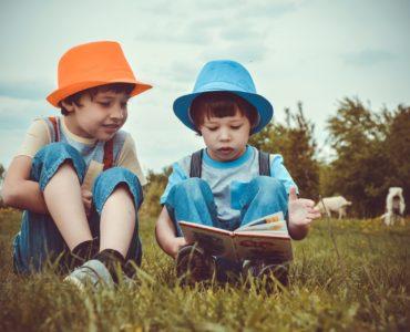 Dzieci czytające książkę na łące